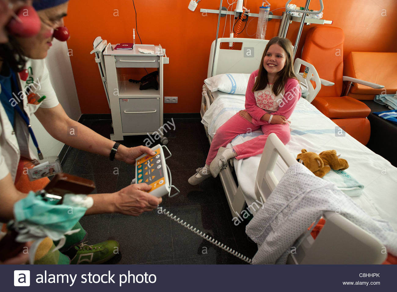 A clown entertains a sick child in a hospital. - Stock Image