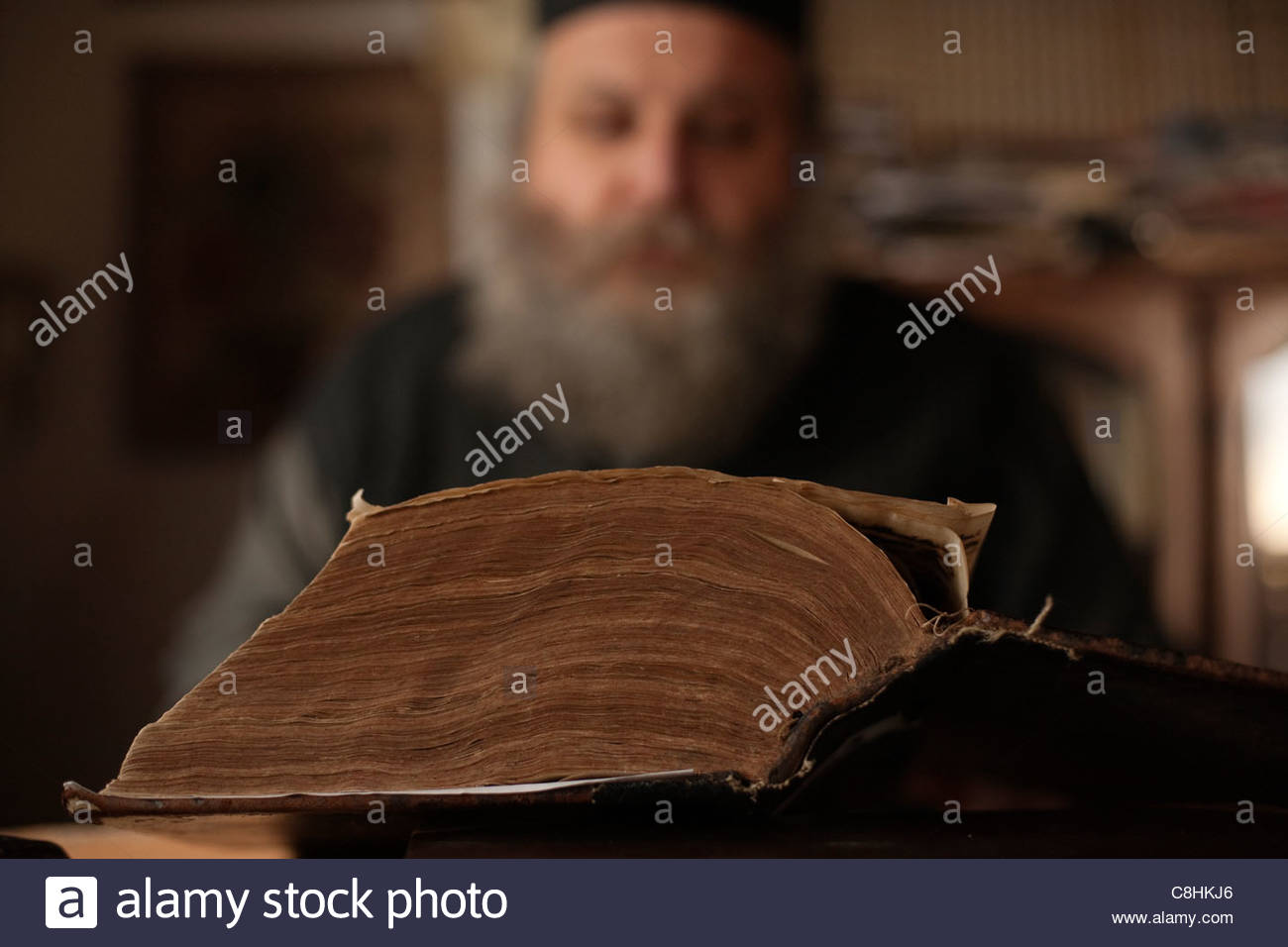 Father Patapios translates ancient Greek texts on his laptop. - Stock Image