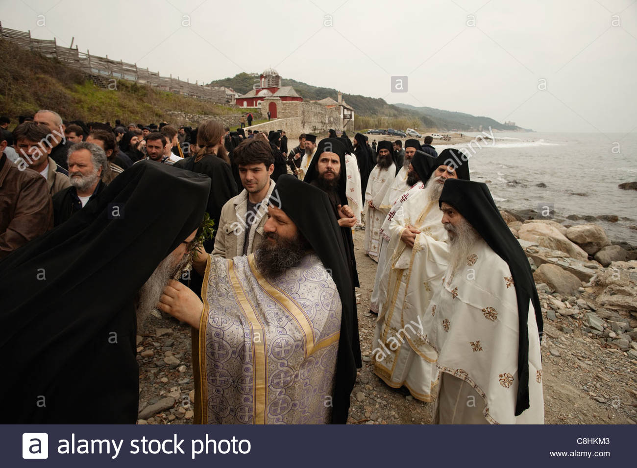 Father David blesses monks with holy water during Portaitissa. - Stock Image