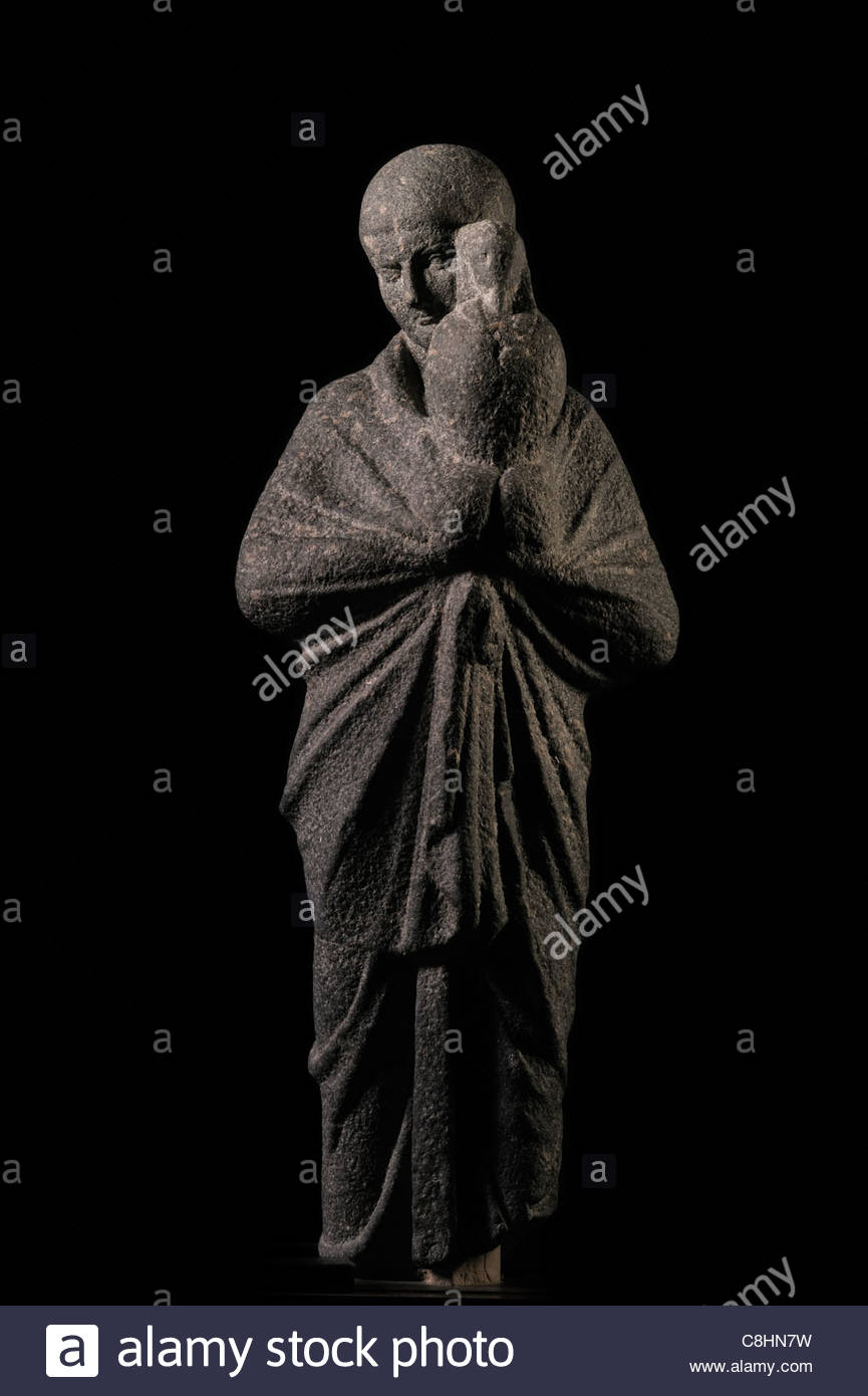 Sculpted in stone, a life-size young priest carries an image of Osiris. - Stock Image