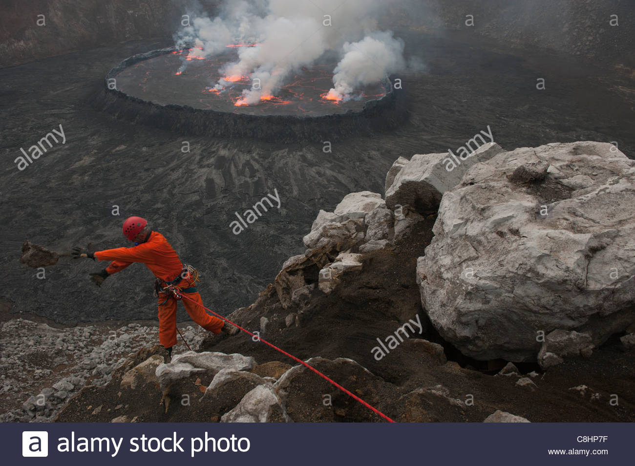 A volcanologist approaches an active lava lake in Nyiragongo volcano. - Stock Image