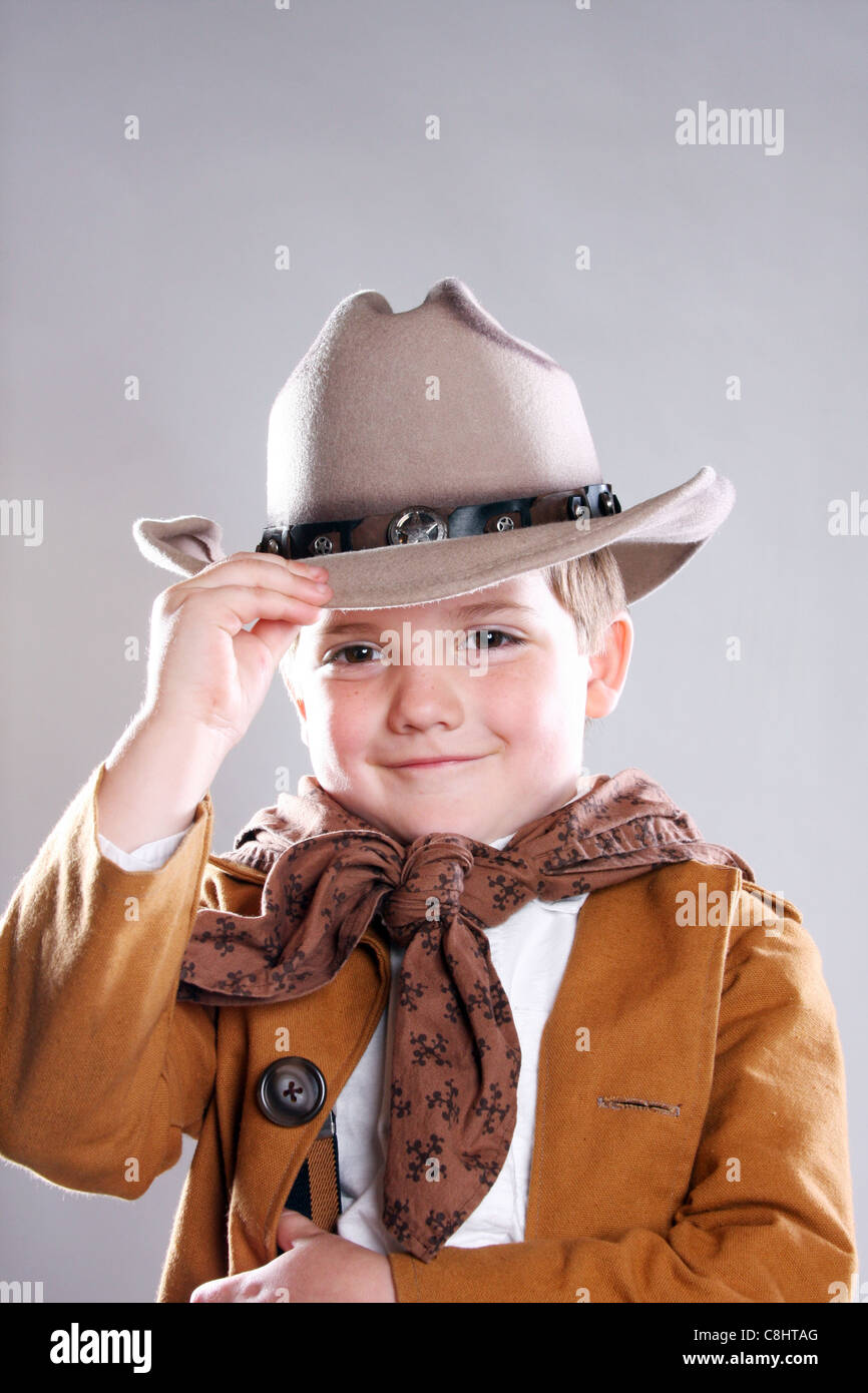 A young cowboy child tipping his hat Howdy in a greeting salute ... 091f8291e342