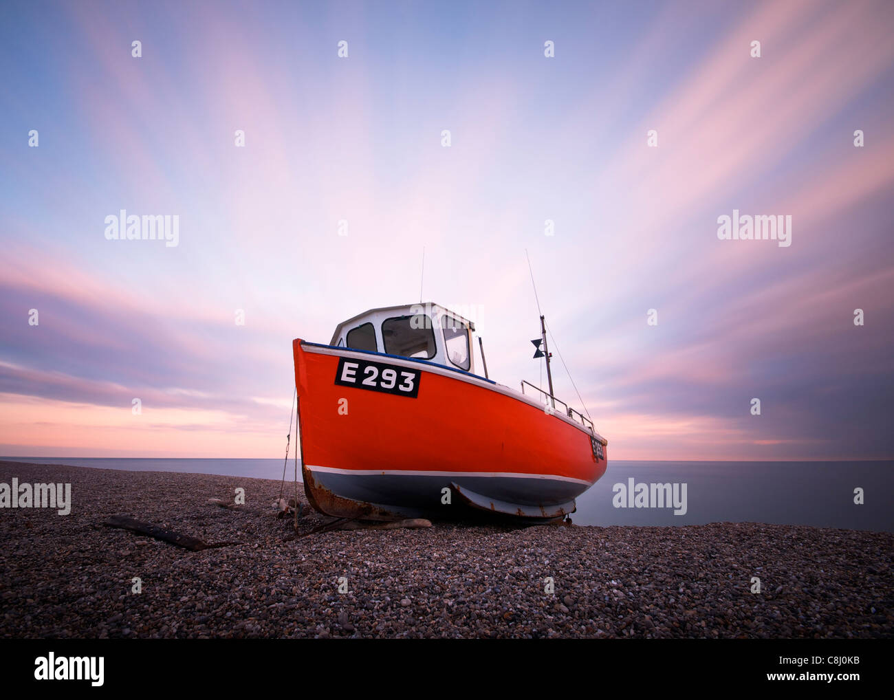 A long exposure of a sunset over a fishing boat in Branscombe East Devon UK - Stock Image