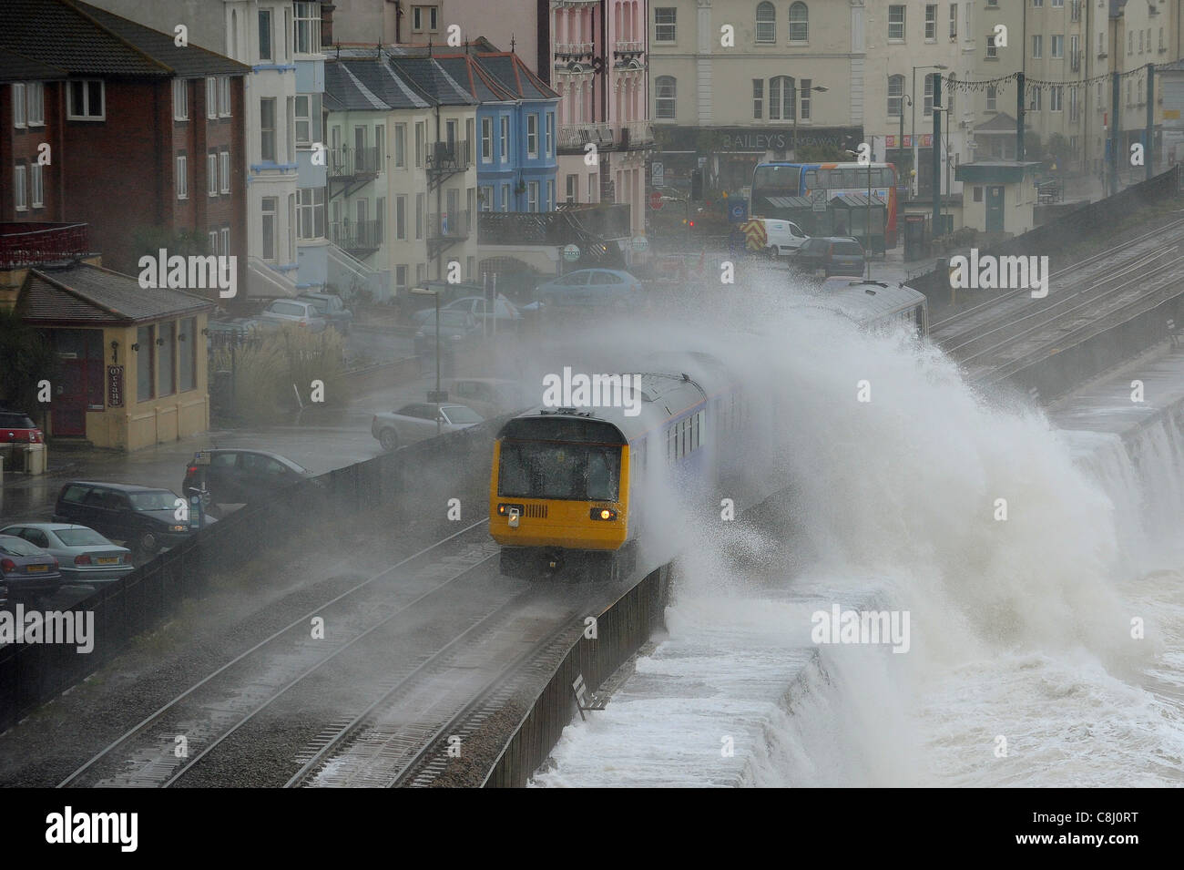 A train is battered by waves as it leaves the station at Dawlish in Devon. - Stock Image