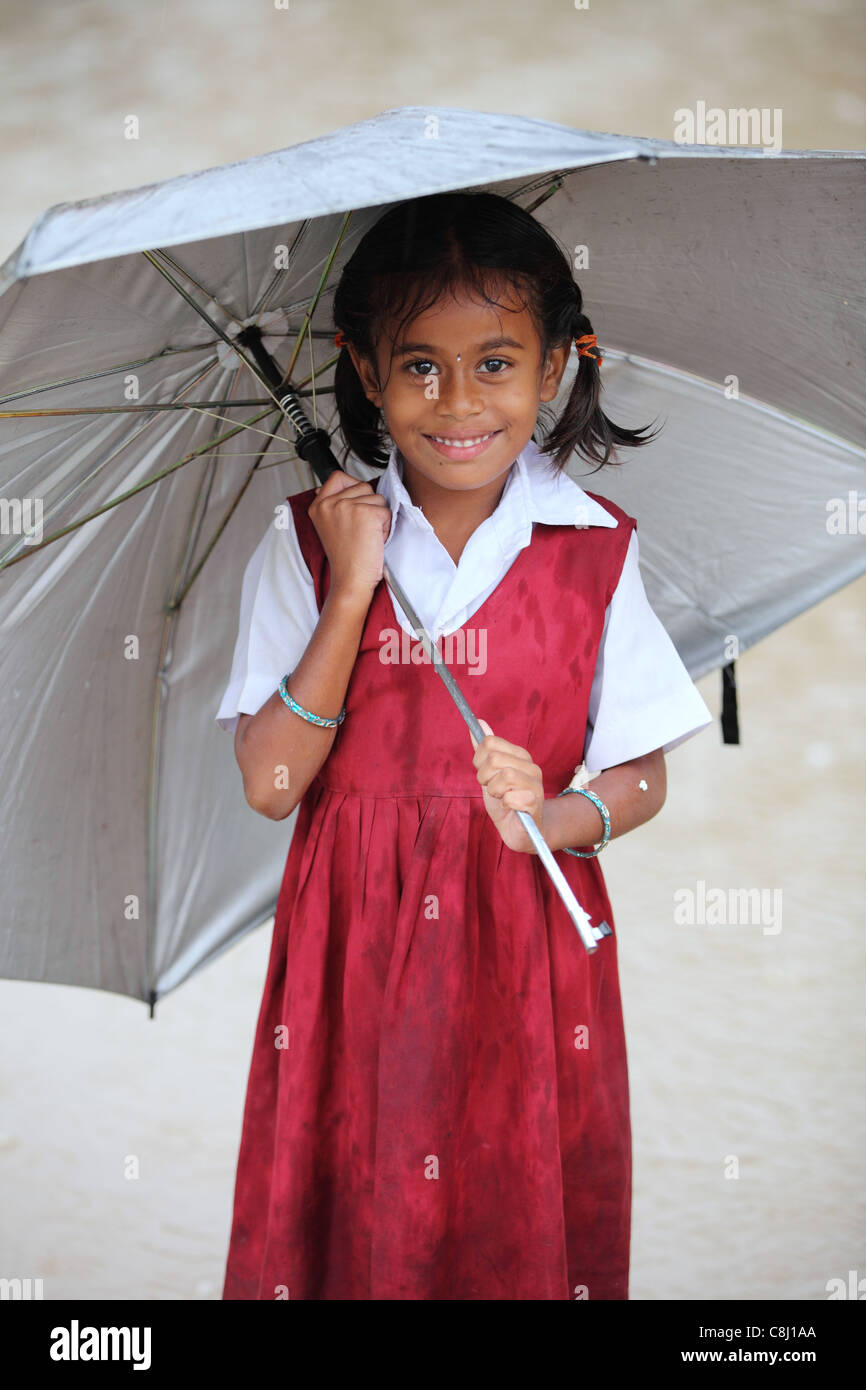 School child under the rain with umbrella Andhra Pradesh South India - Stock Image