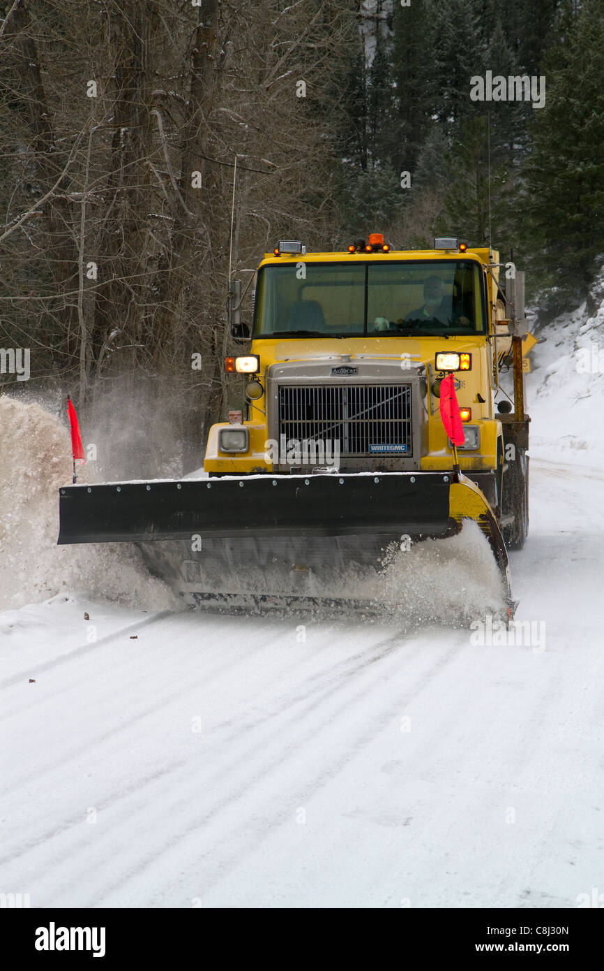 Snowplow removing snow from the road at Grimes Creek, Boise County, Idaho, USA. - Stock Image