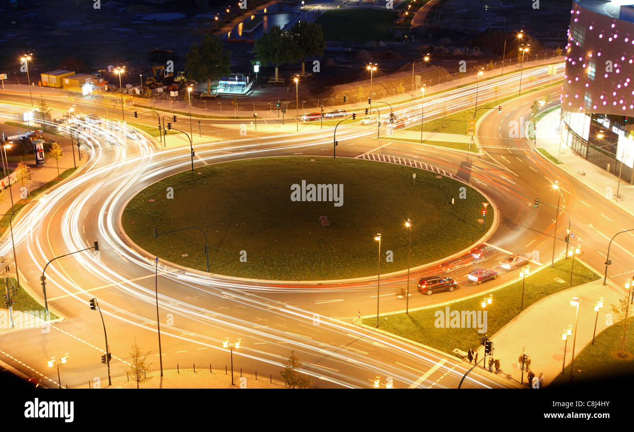 Roundabout in a city. At night, lights of cars around the circle. Controlled by traffic lights. - Stock Image