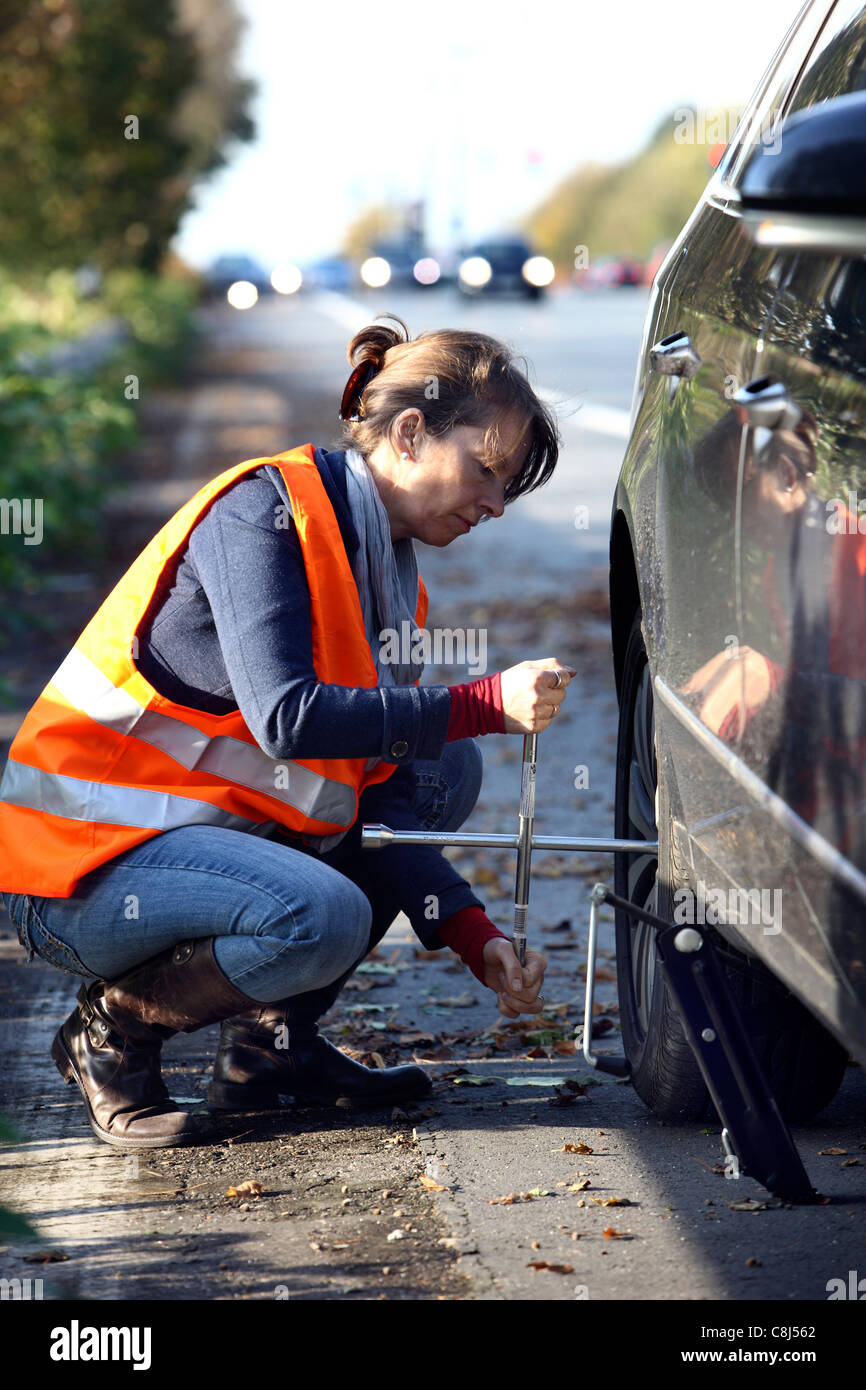 Car breakdown, flat tire. Woman changes a tire of a car on a highway, wearing a high visibility vest. Stock Photo