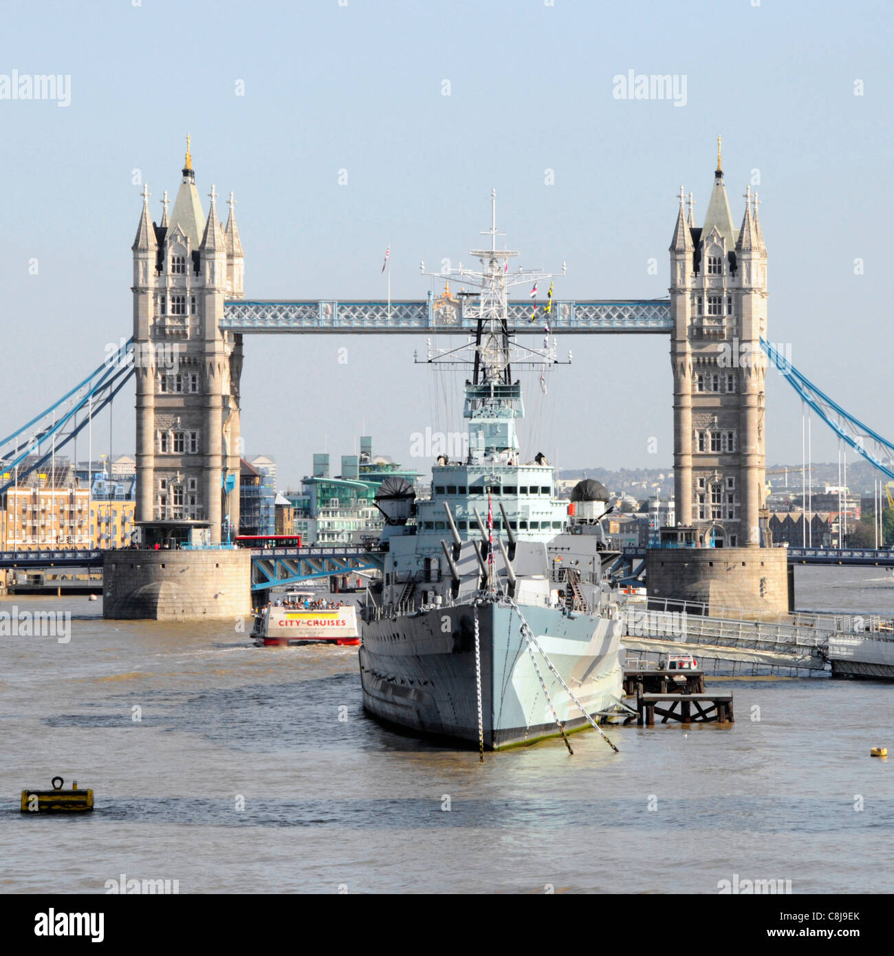 Light Cruiser HMS Belfast part of Imperial War Museum moored in River Thames in The Pool of London with iconic Tower - Stock Image