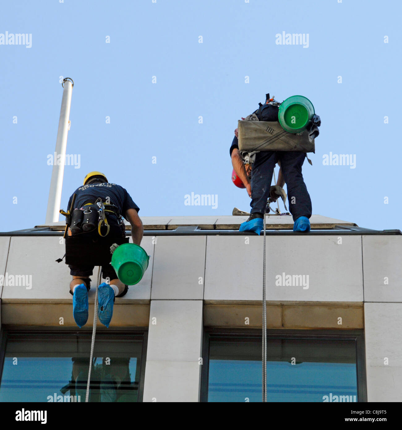 Close up of window cleaner workers abseiling from roof level down face of office block London England UK Stock Photo