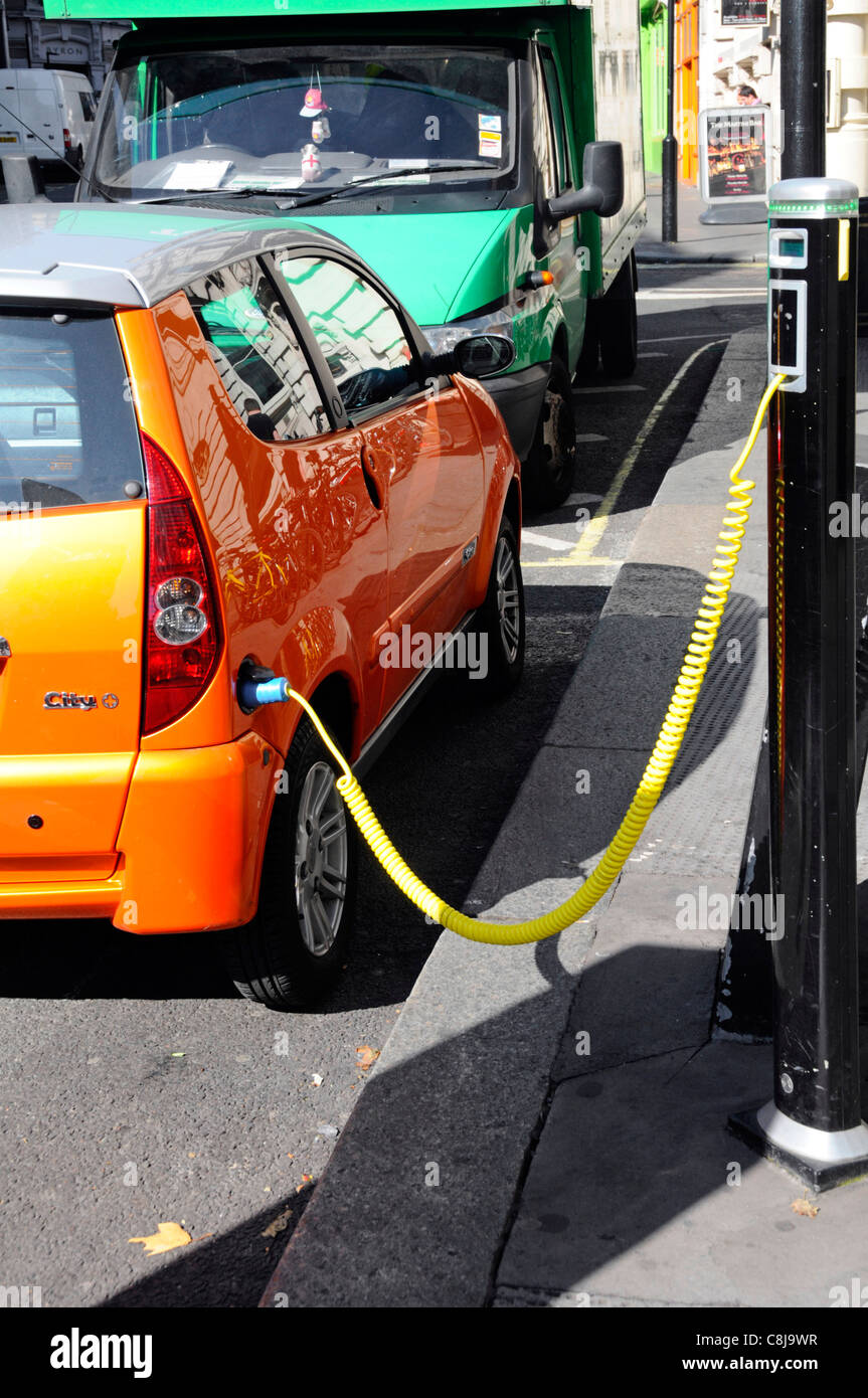 Electric car charging station cable hooked up to recharging bollard London UK - Stock Image