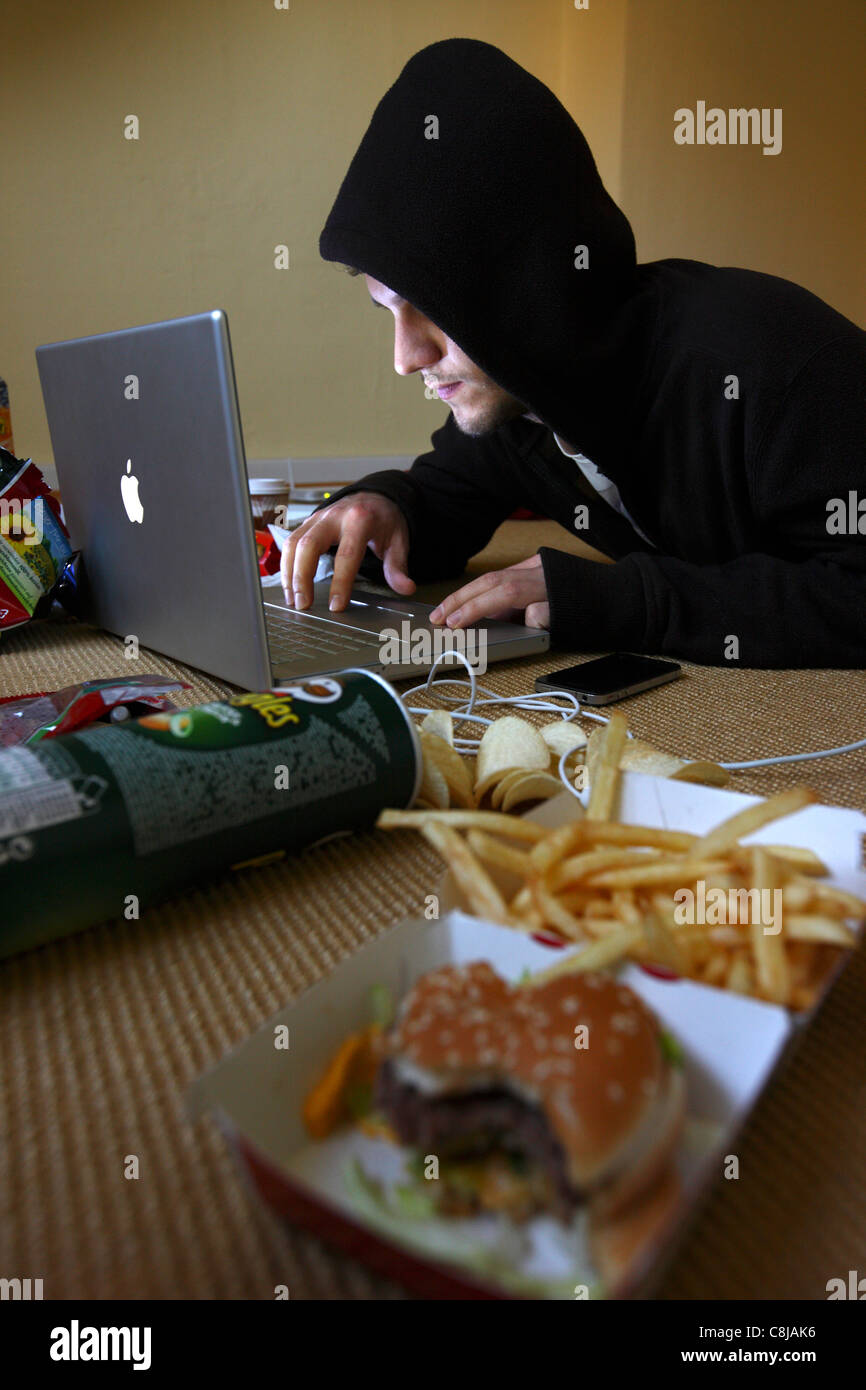 Computer user, hacker, sits conspiratorially, in an empty apartment,  with a laptop. Symbol picture, computer-Internet - Stock Image