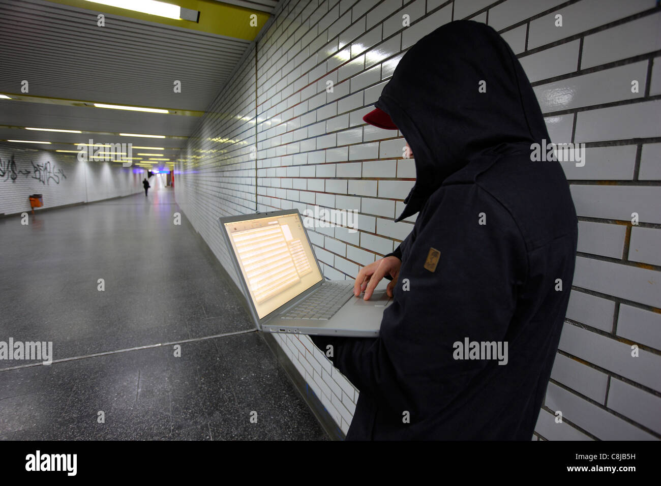 Computer user, hacker, sits conspiratorially with a laptop, in a subway station. Symbol picture, computer-Internet - Stock Image
