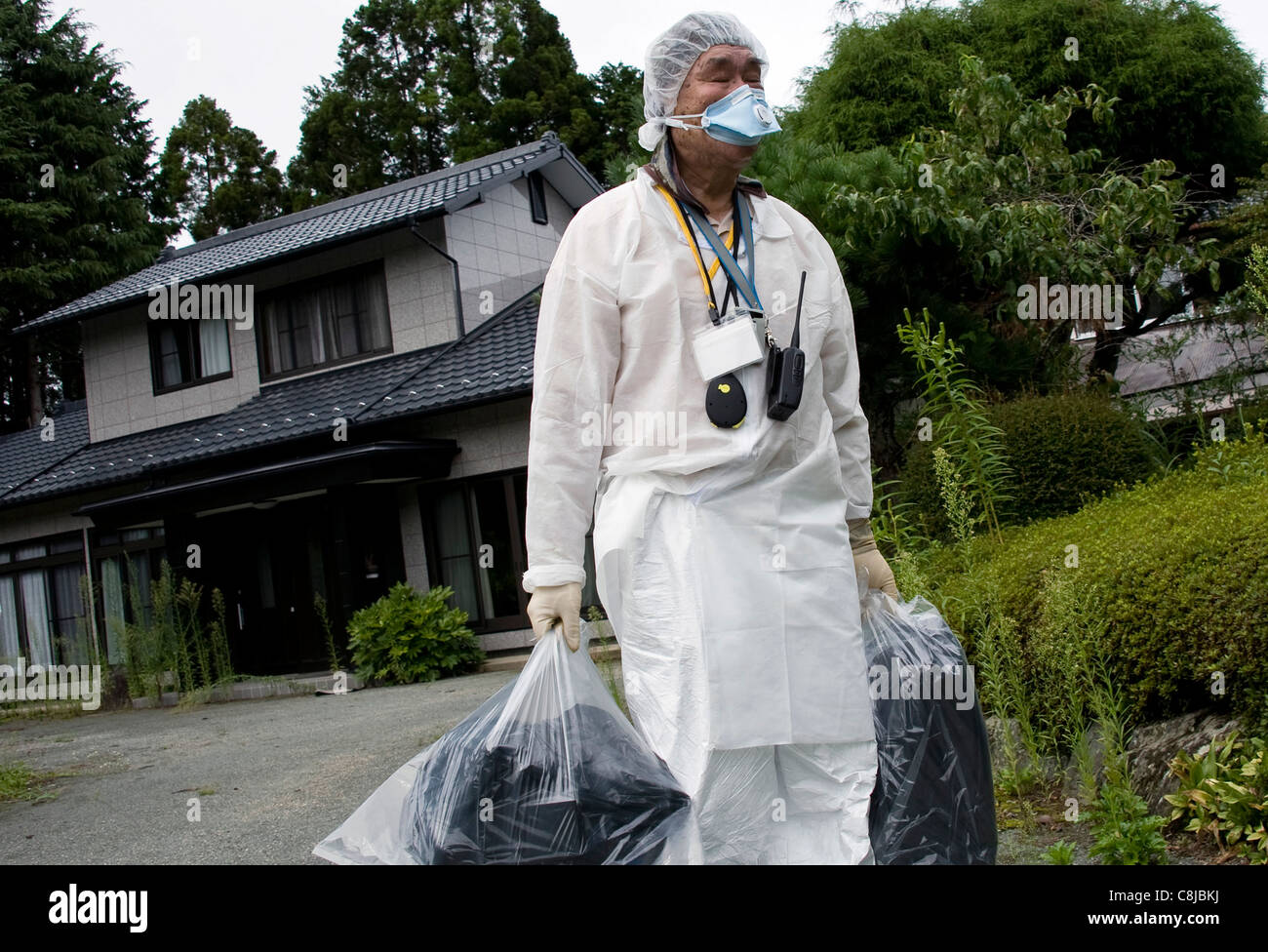 Takashige Kowata leaves his home for what he believes will be the last time in Okuma near the leaking Fukushima - Stock Image