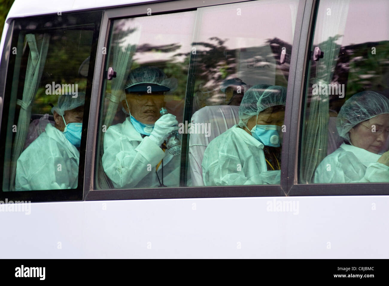 Residents sit in a bus after being allowed briefly to return to their homes in Okuma, about 1.5 km from the No. - Stock Image