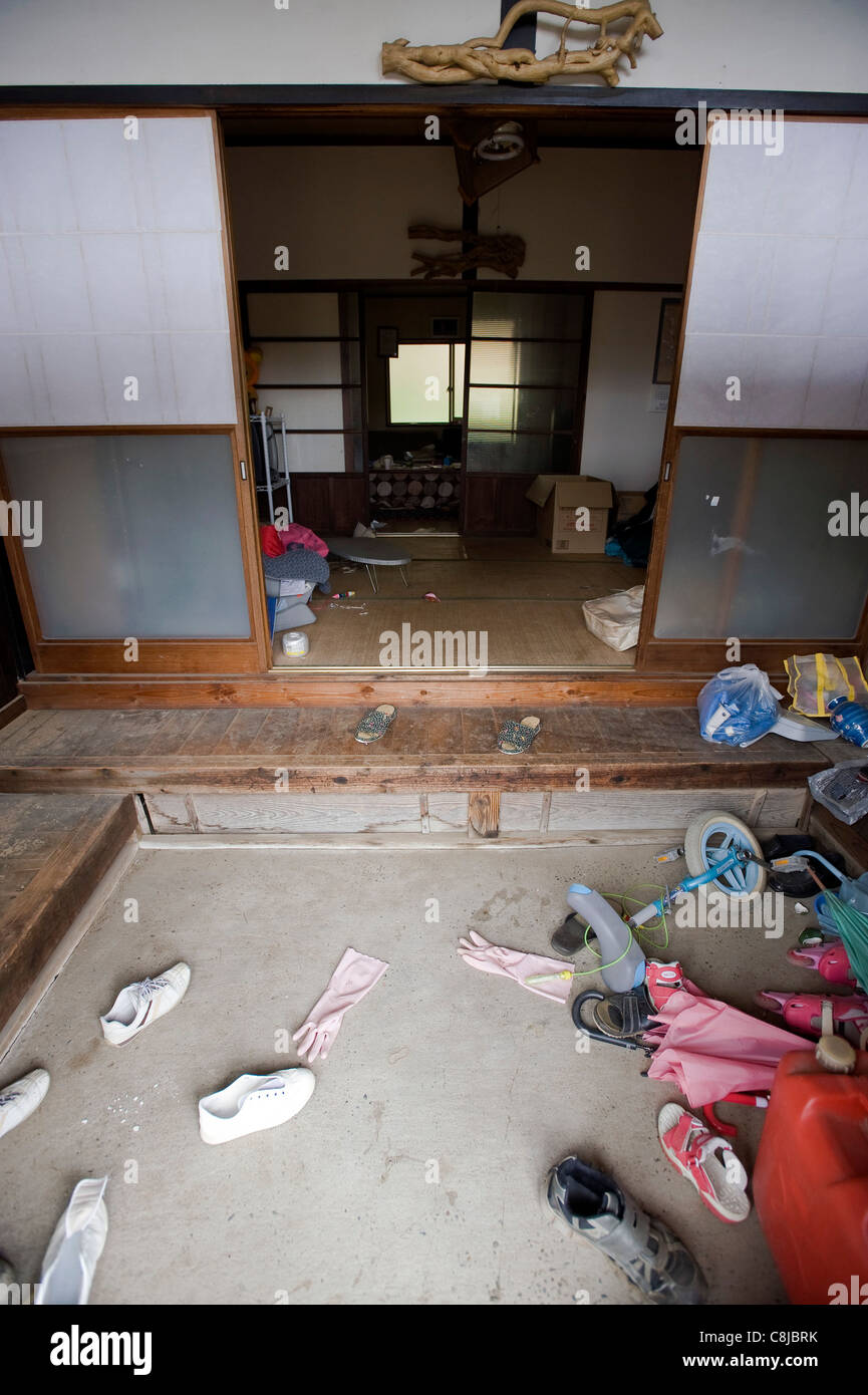 Belongings scattered about in a home inside the exclusion zone around the damaged Fukushima No. 1 nuclear power - Stock Image