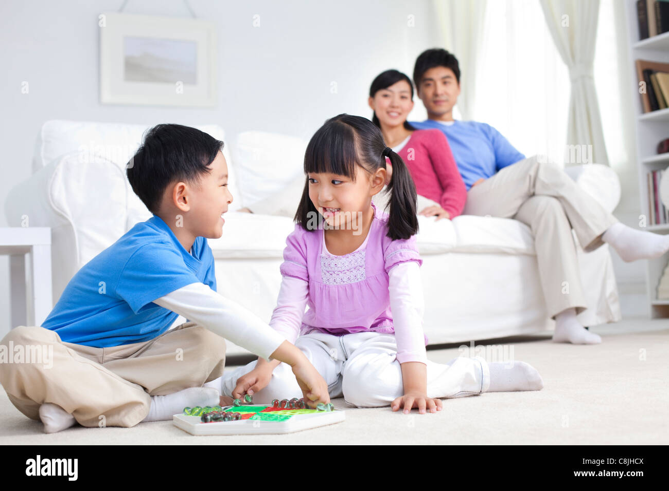 Chinese children playing with toys on the floor with parents behind them - Stock Image