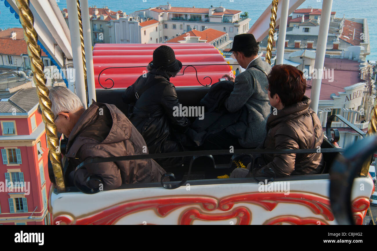 Nice, France, Chinese Tourists Riding on Ferris Wheel in Town Square, Annual Carnival Events on Street Stock Photo
