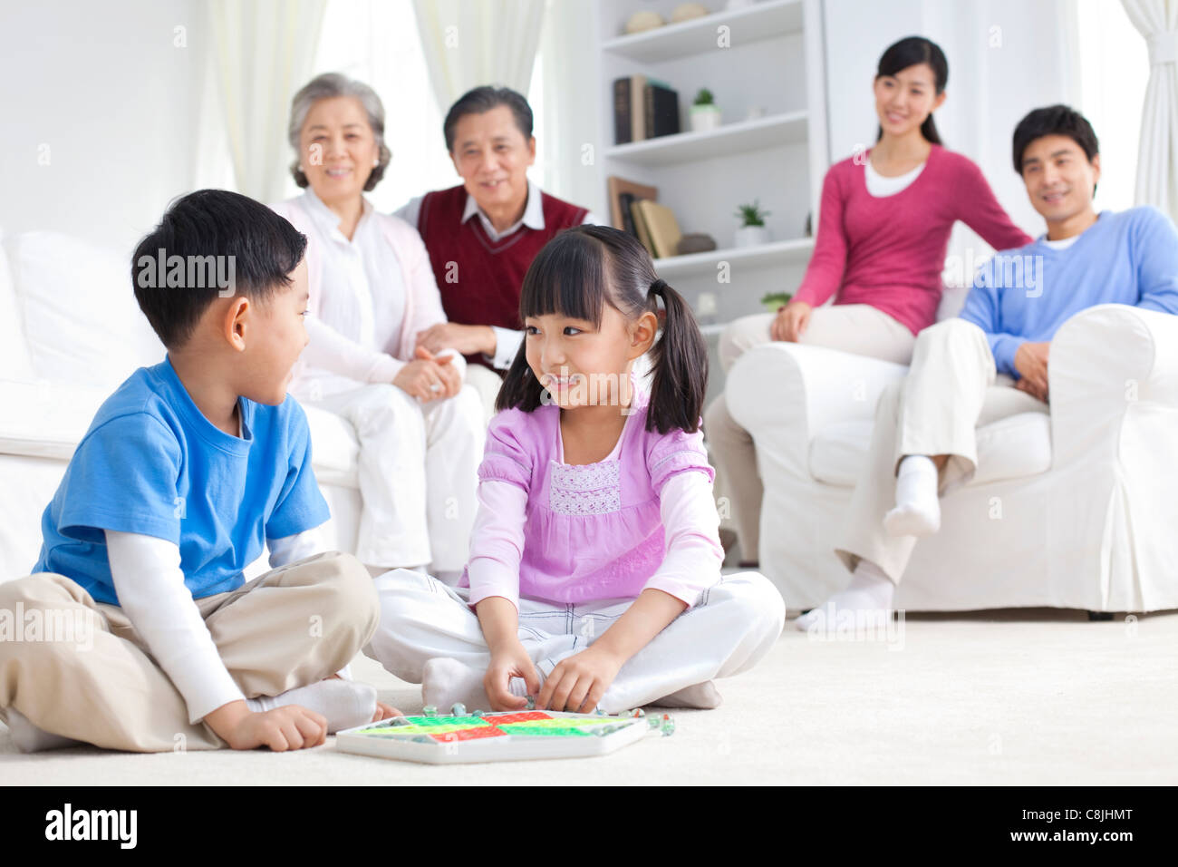 Chinese children playing with toys on the floor with grandparents and parents behind them - Stock Image