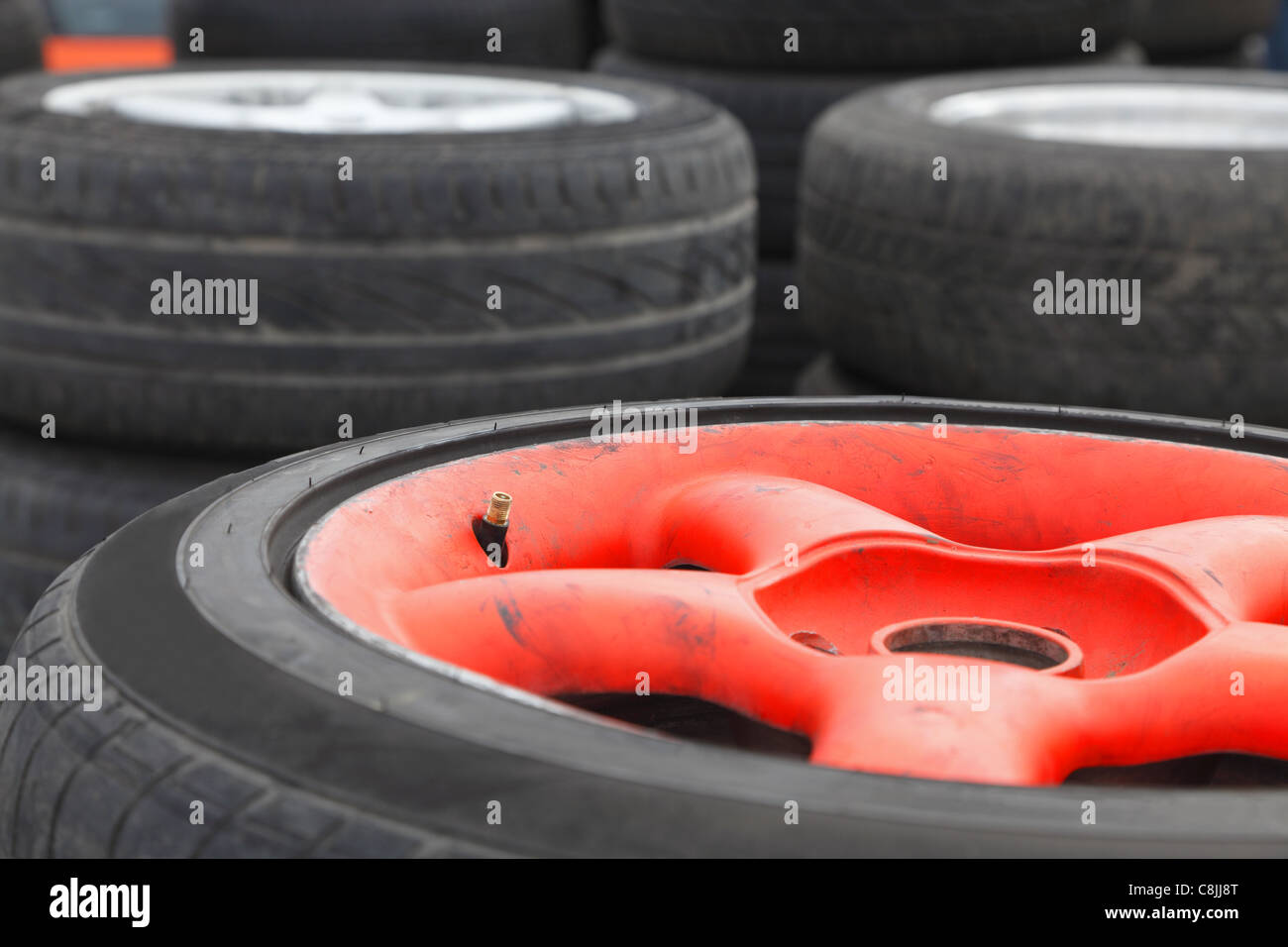 Image of a heap of race car wheels. Selective focus on the tire valve. - Stock Image
