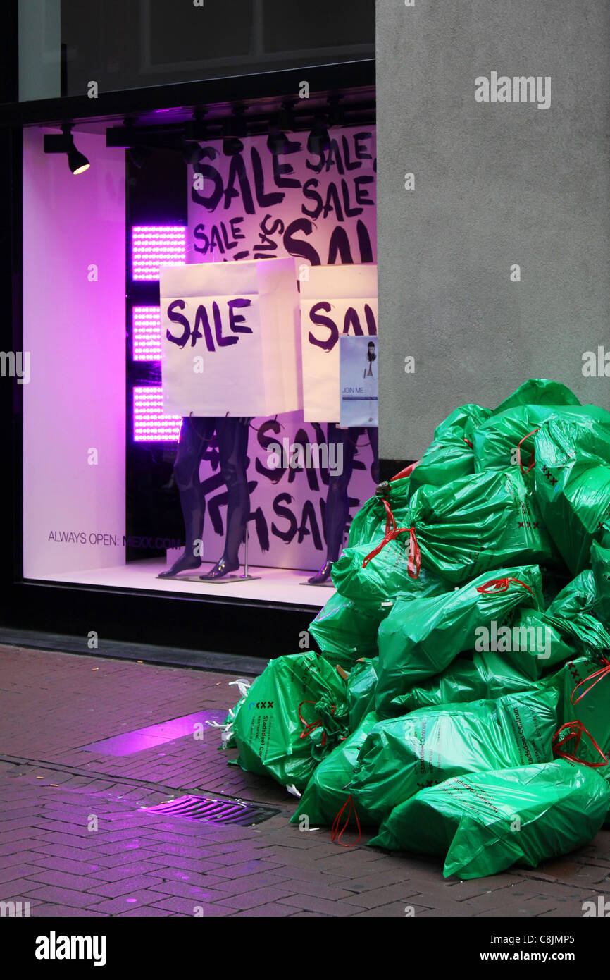 Green rubbish bags ans violet Sale signs showcase shop - Stock Image