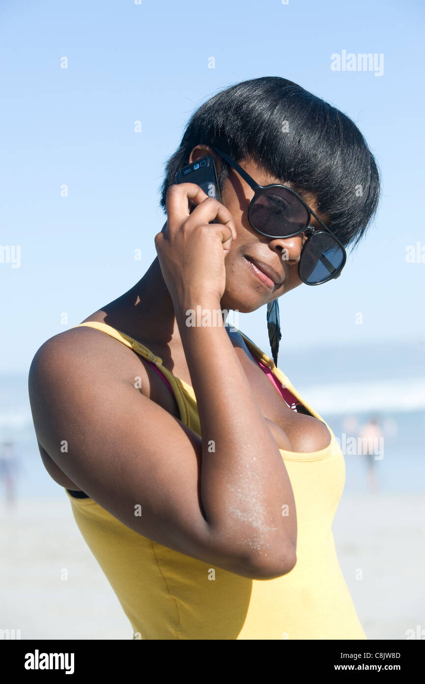 Teenager makes a phone call with her mobile phone Grotto Beach Western Cape South Africa - Stock Image