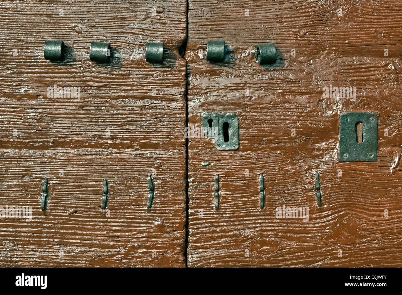 three different locks and latches on an old Italian wooden door - Stock Image