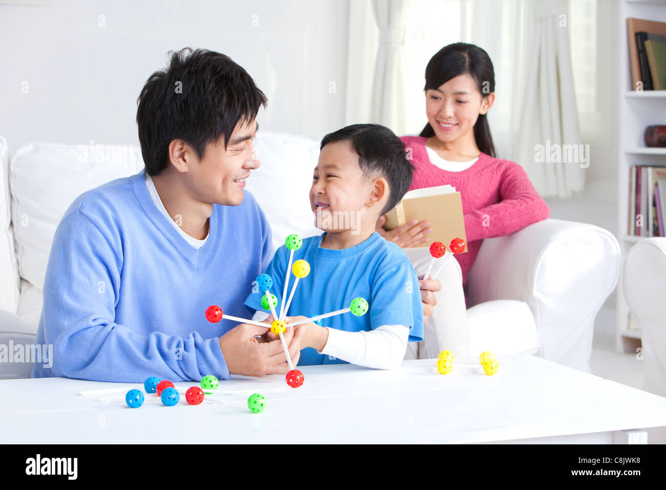 Young Chinese boy with parents and toys in the living room - Stock Image