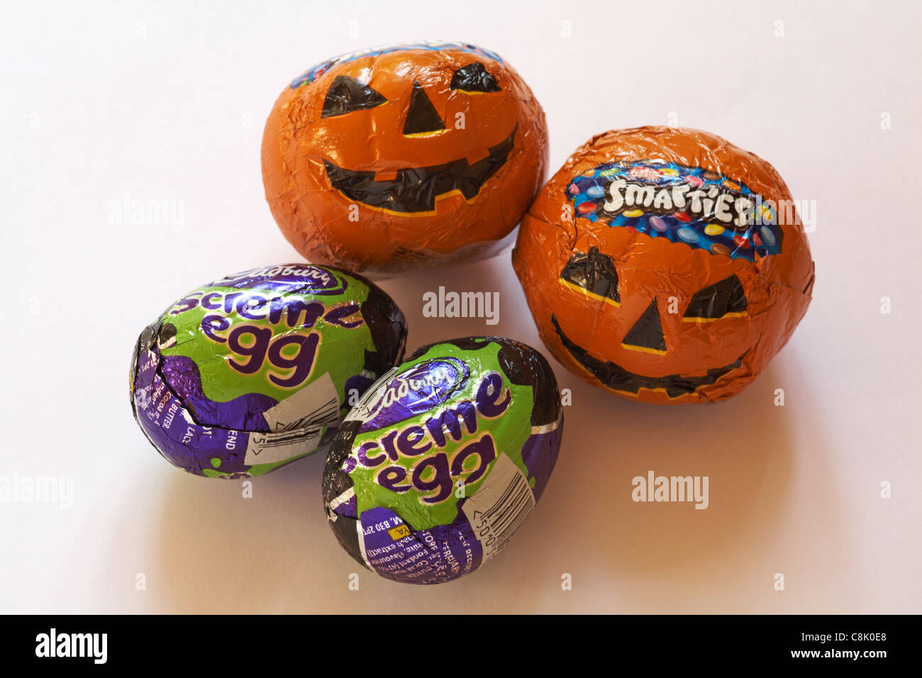 Halloween chocolates - two Cadbury screme eggs, screme egg, and two smarties pumpkin faces isolated on white background - Stock Image