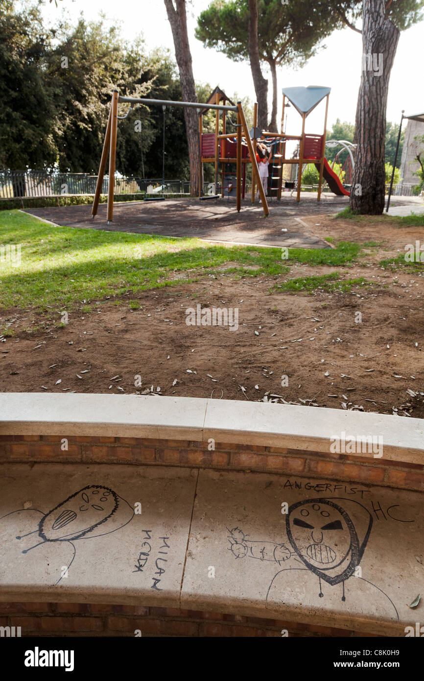 graffiti on concrete park bench with swings and climbing frame - Stock Image