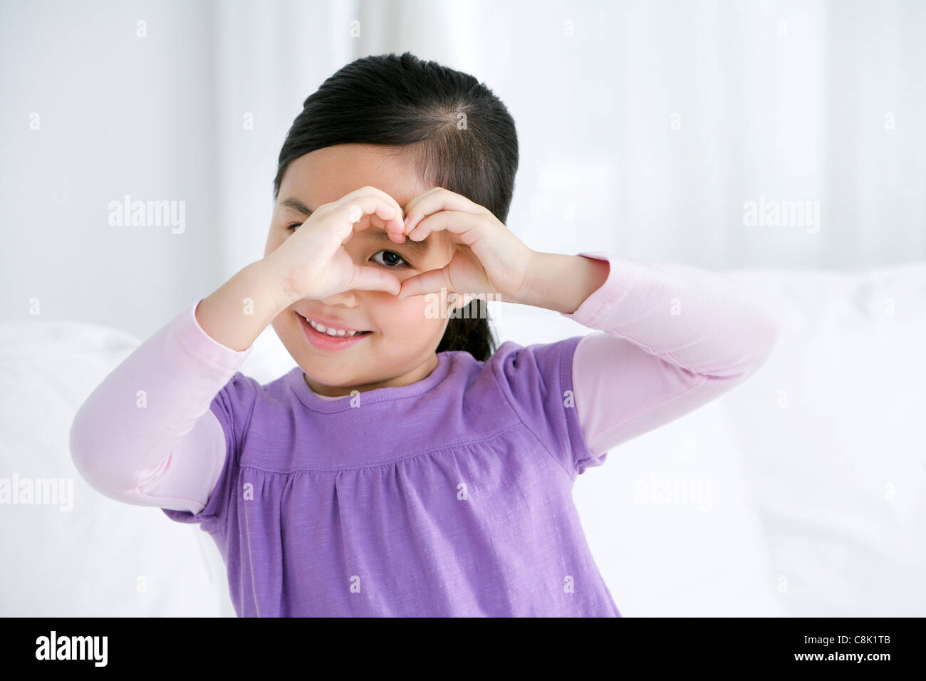 Chinese girl hands in heart shape - Stock Image