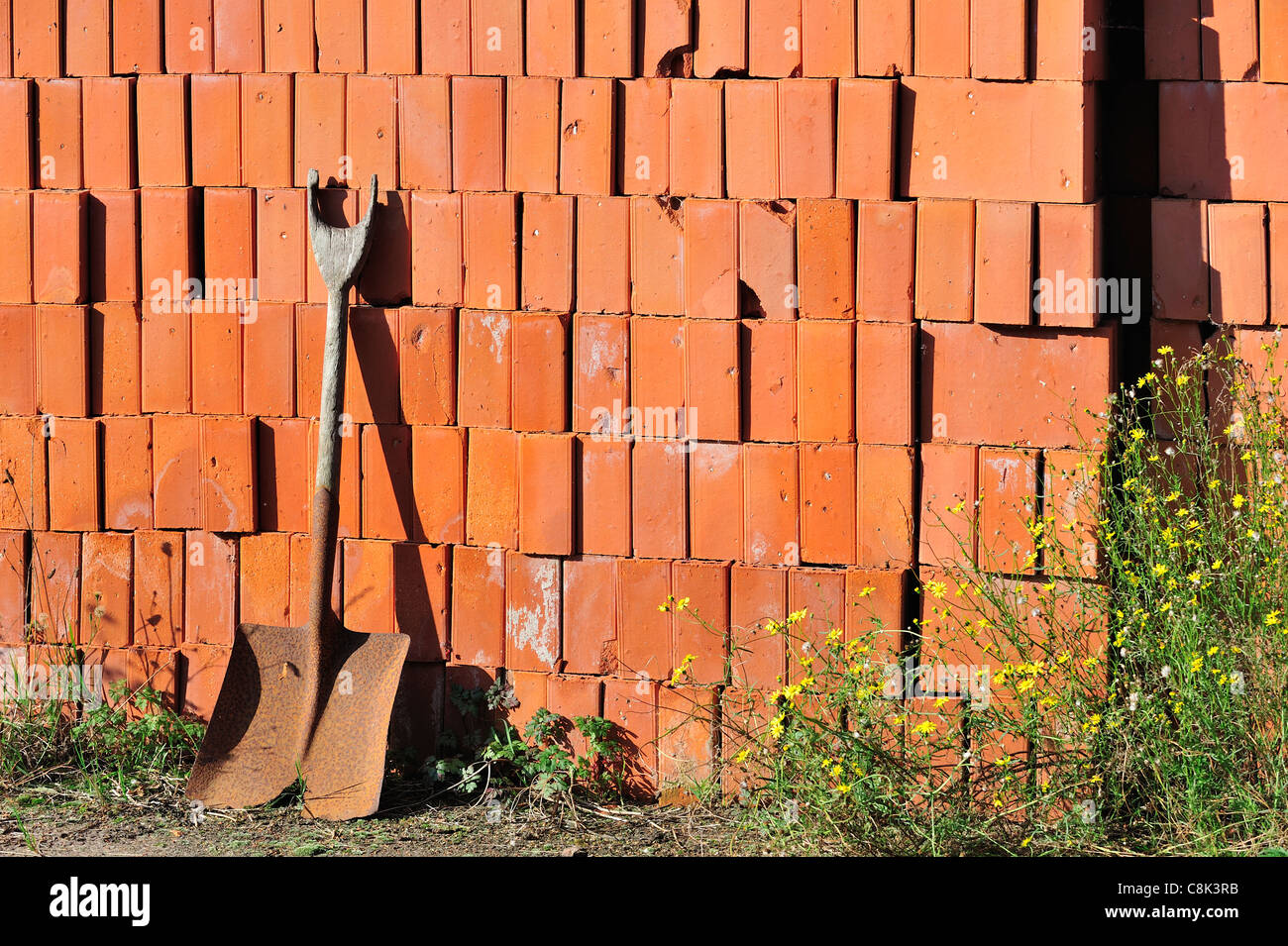 Shovel and pile of stacked red bricks as building material at brickworks, Boom, Belgium - Stock Image