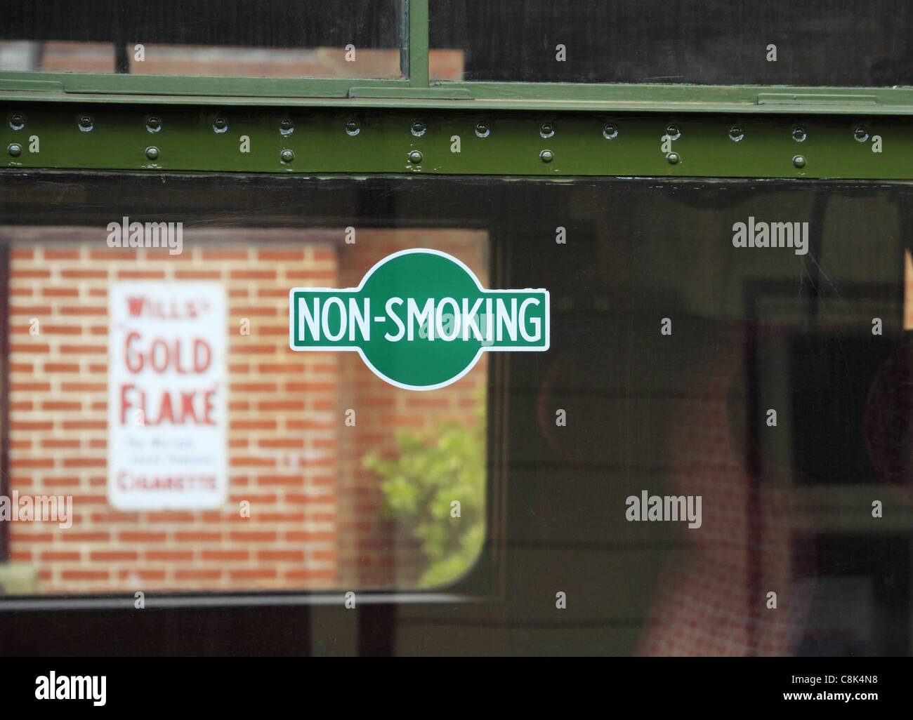 A no smoking sign on a train window juxtaposed with an old cigarette ad at The Bluebell Railway, Sheffield park, - Stock Image