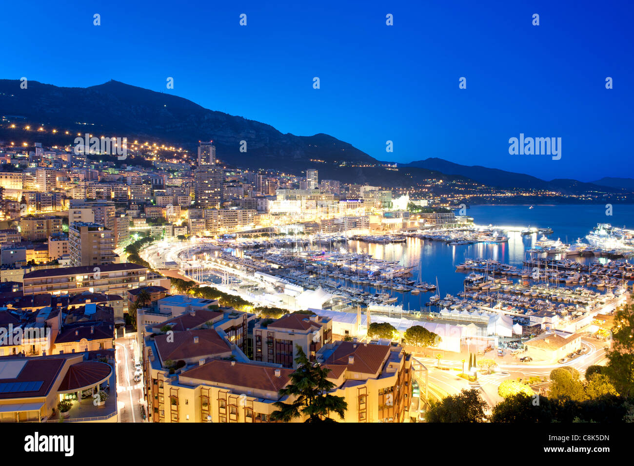 Dusk view of Port Hercule and the city and Principality of Monaco on the French Riviera along the Mediterranean - Stock Image
