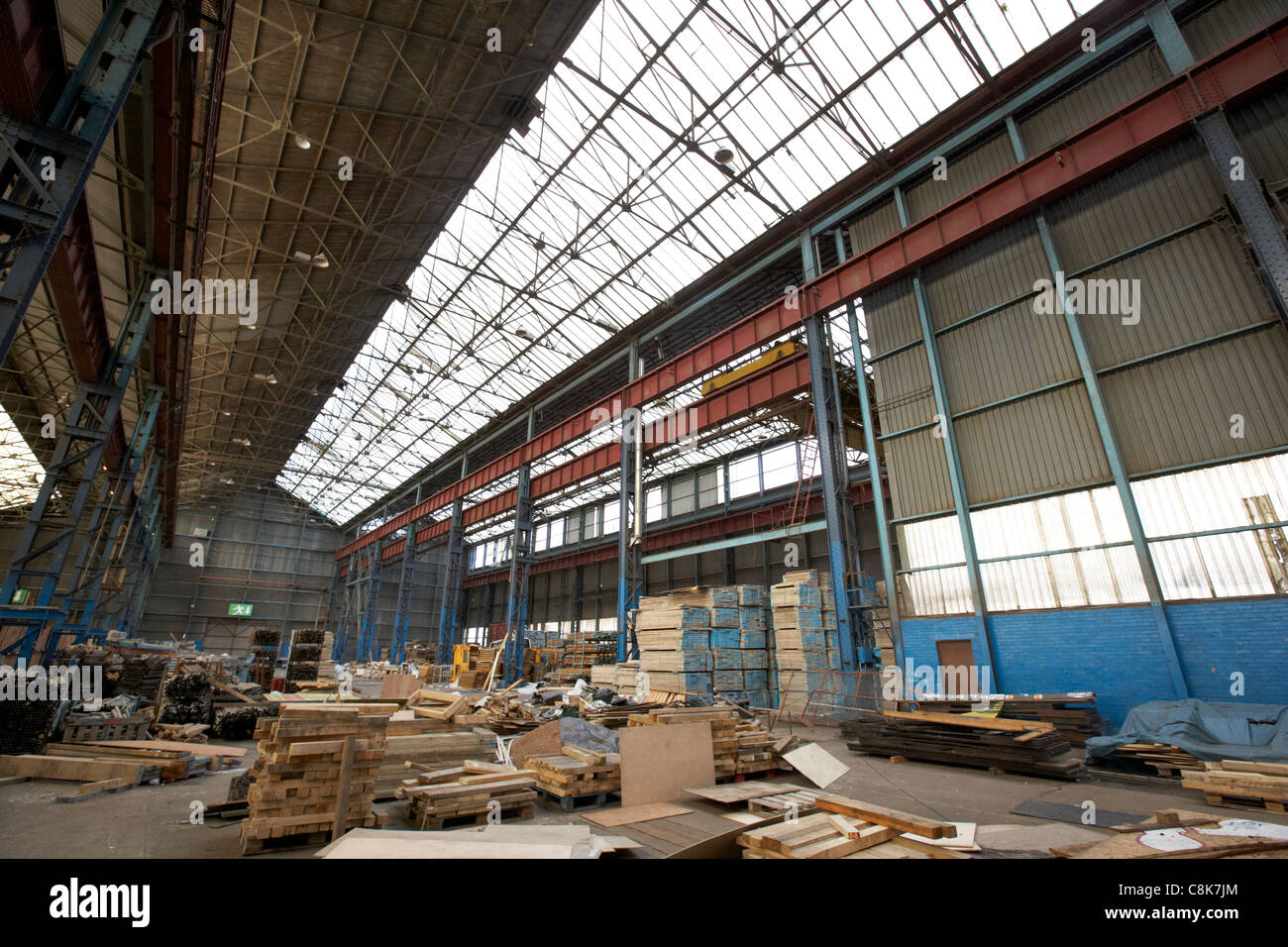 interior of an old factory warehouse unit containing building materials belfast northern ireland uk - Stock Image