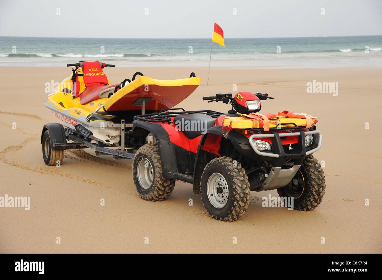 Cornwall, England.  An RNLI lifeguard's quad bike and jet ski PWC rescue craft on a sandy beach. - Stock Image