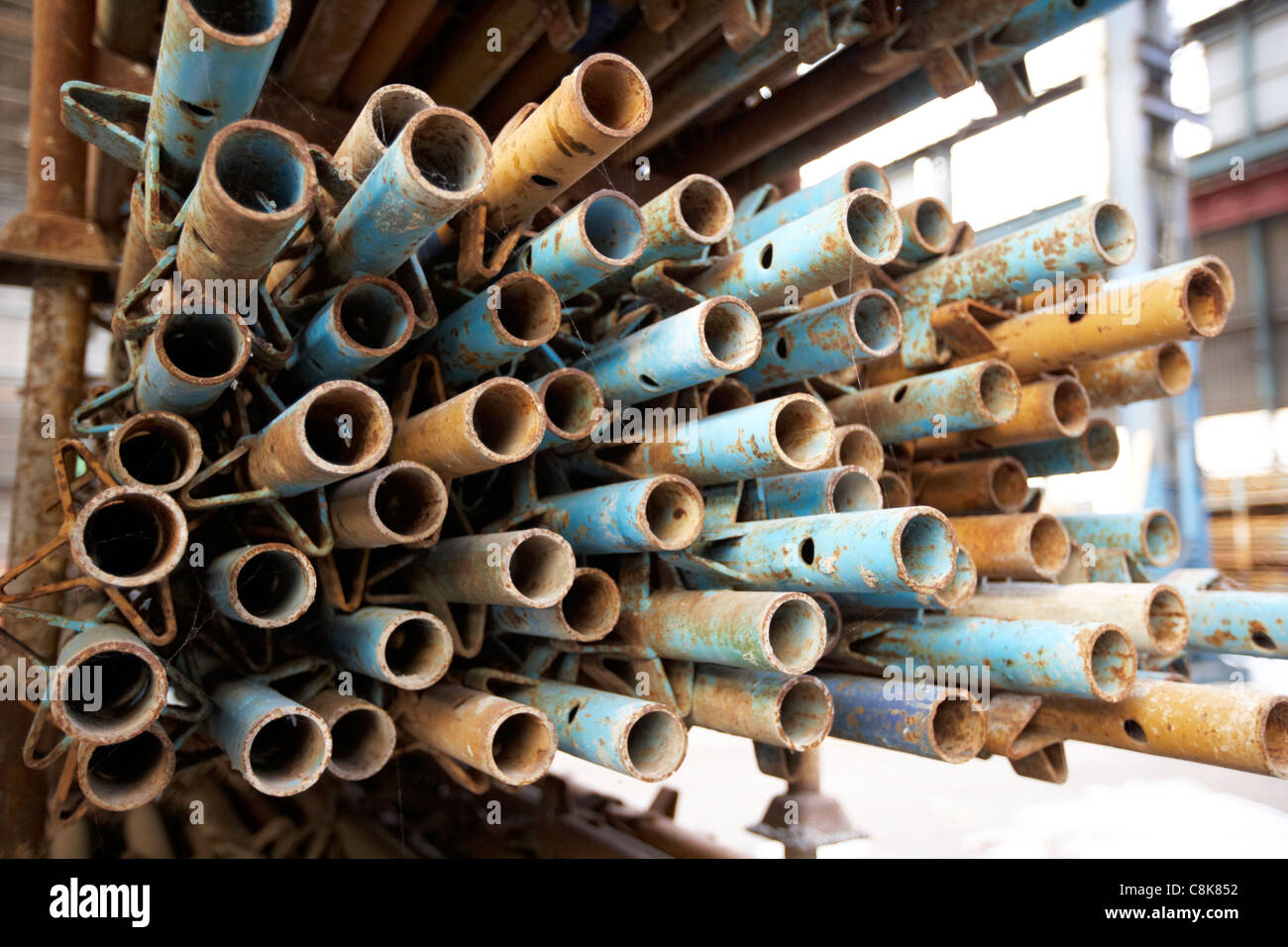 pile of used scaffolding poles stored in an old factory warehouse unit belfast northern ireland uk. - Stock Image