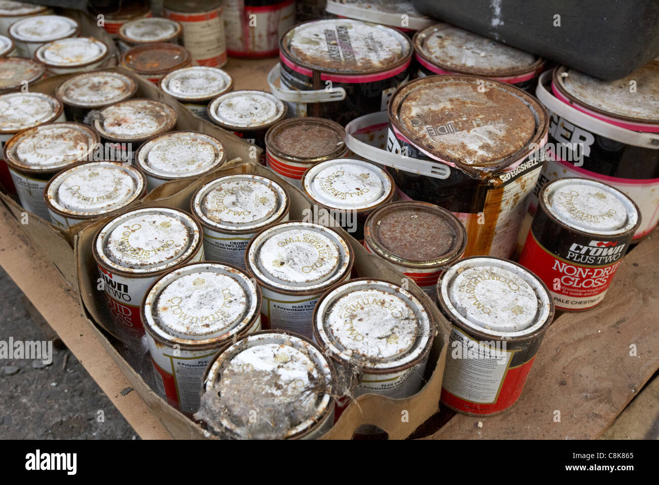 pile of old crown tins of paint rusting and covered in dirt in an old factory warehouse unit belfast northern ireland - Stock Image
