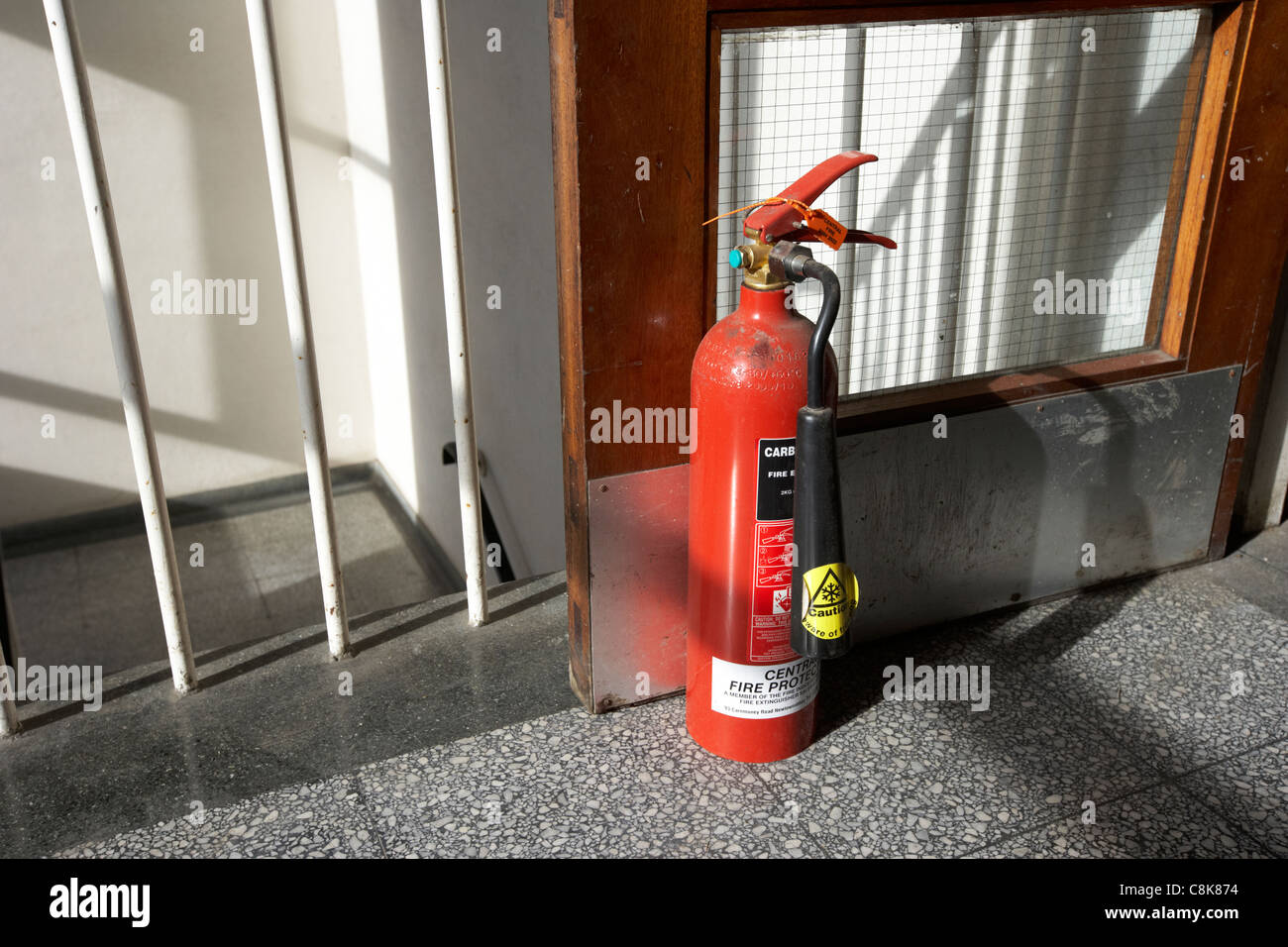 fire extinguisher holding a fire door open at the top of a set of stairs in an old factory warehouse unit - Stock Image