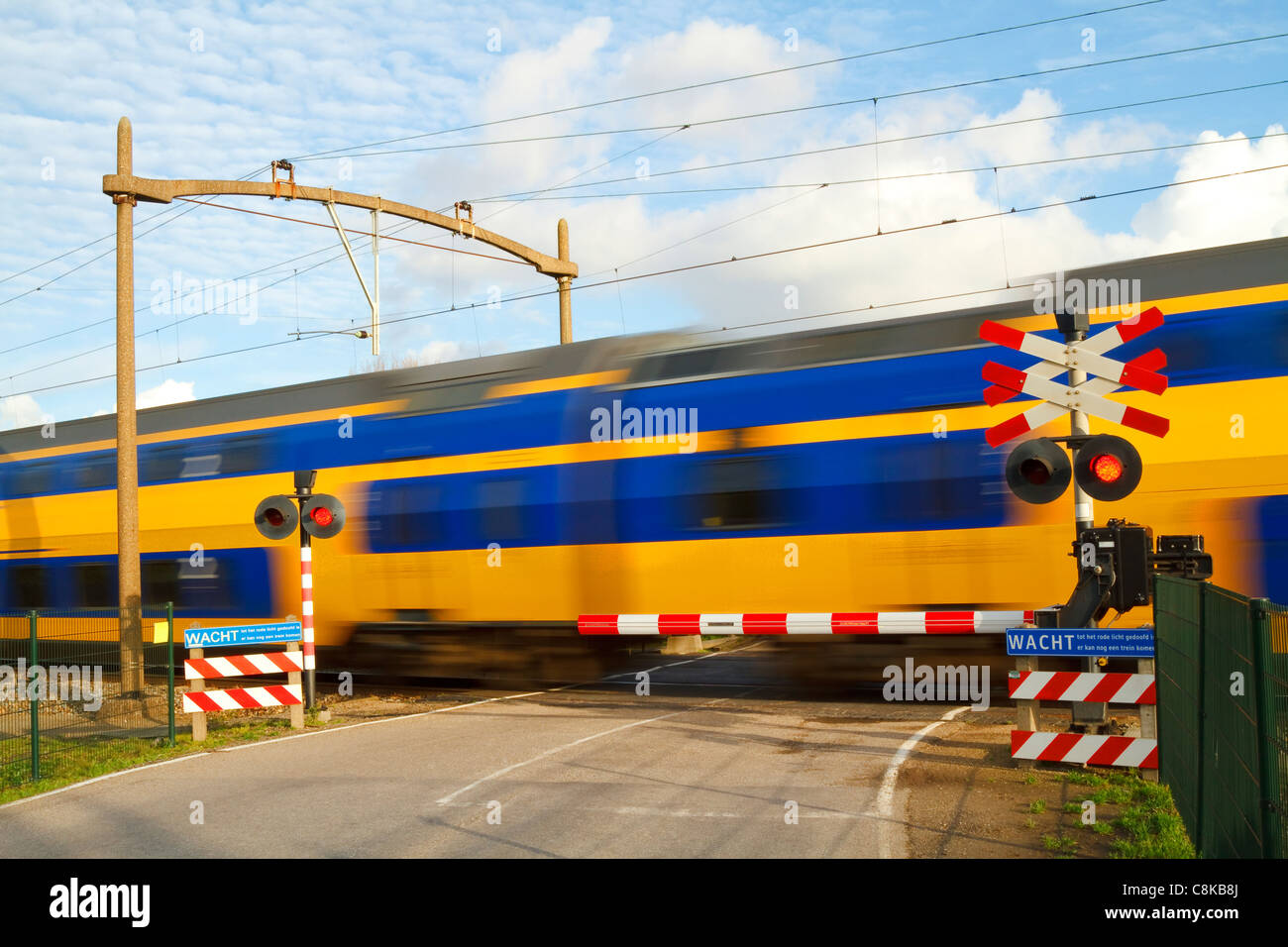 Dutch yellow and blue intercity high speed train passing a railway crossing with the barrier down and flashing warning - Stock Image