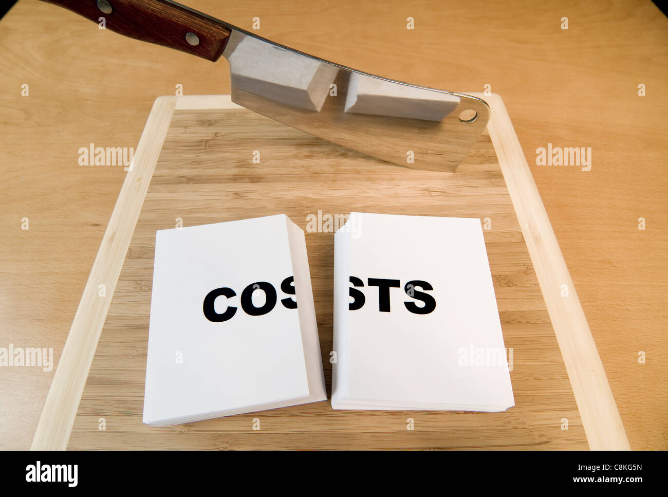 Cutting costs in business or personal finances with a cleaver. - Stock Image