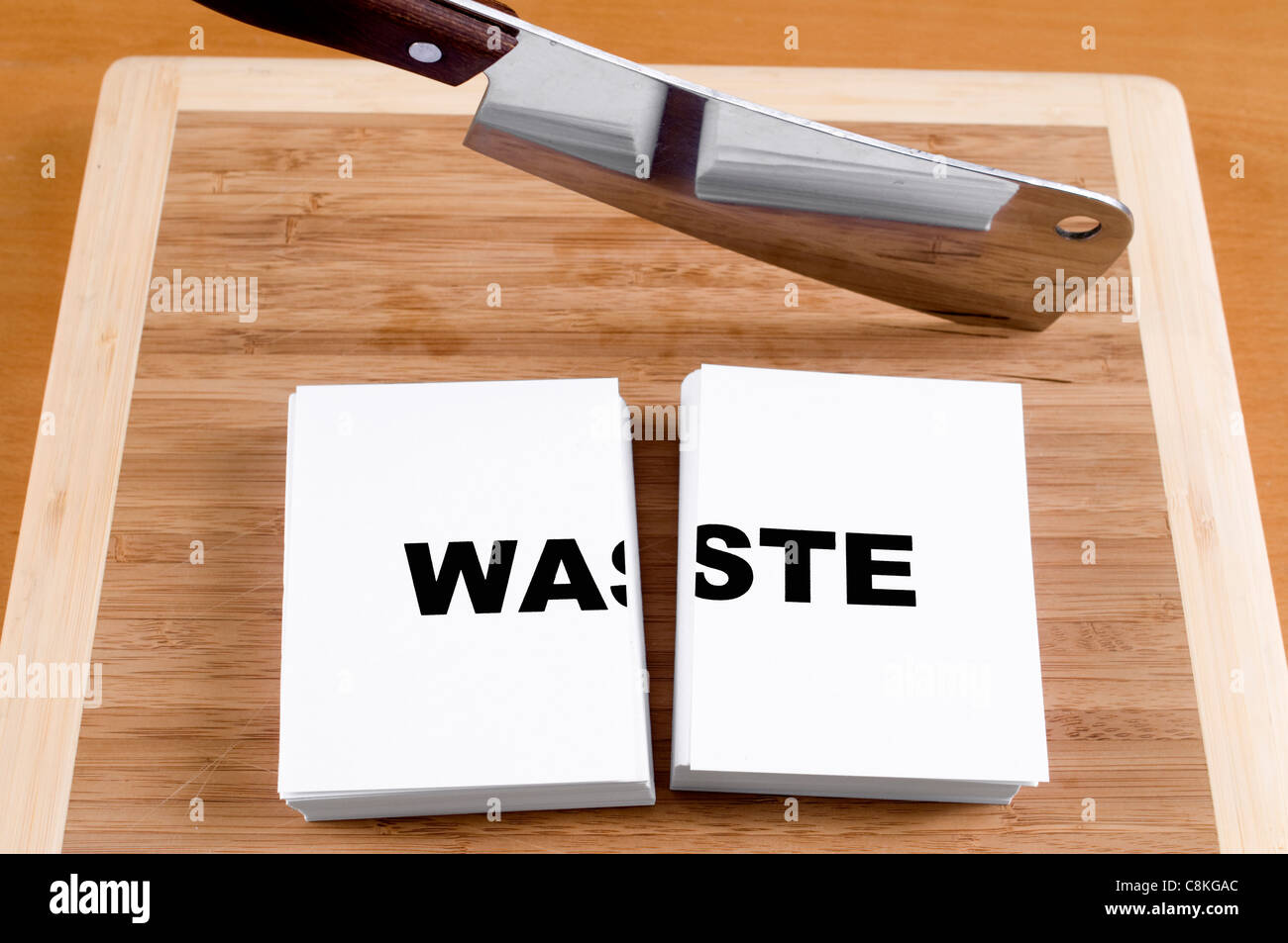 Cutting Waste with a Cleaver and Cutting Board. - Stock Image