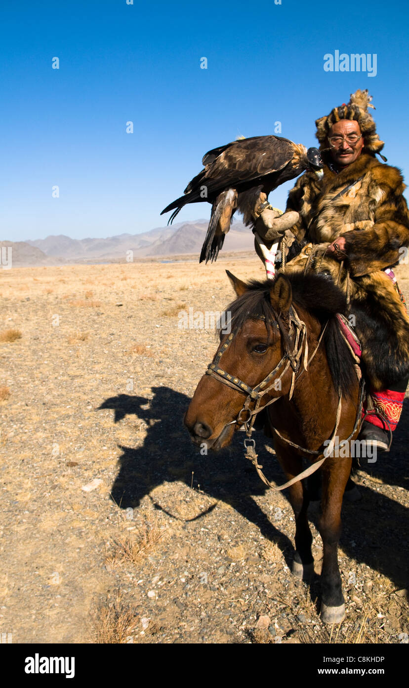A Kazakh eagle hunter with his Golden Eagle in the Altai region of western Mongolia. - Stock Image