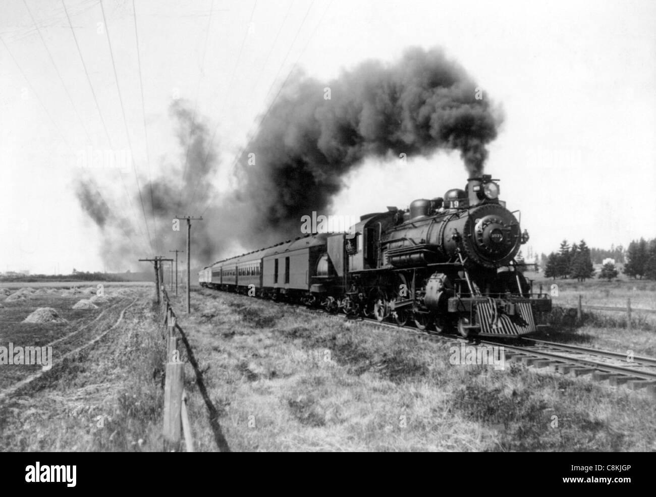 Steam train moving down the tracks circa 1900 - Stock Image