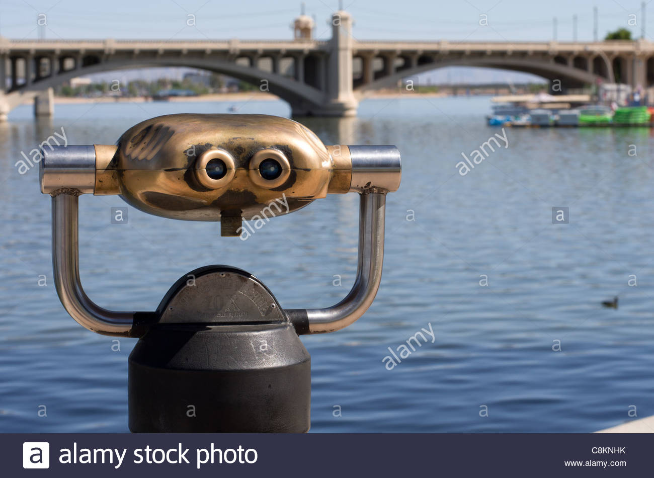 Coin-operated binoculars look out over Tempe Town Lake and the Mill Avenue Bridge in Tempe, Arizona. - Stock Image