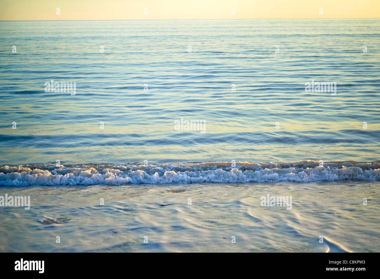 Gentle surf at serene sunset - Stock Image