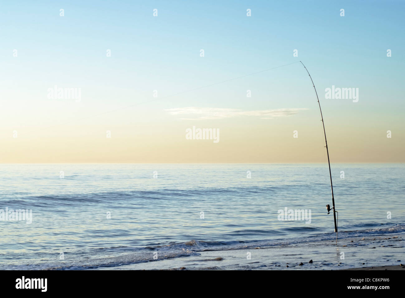 Fishing rod in gentle surf at serene sunset - Stock Image