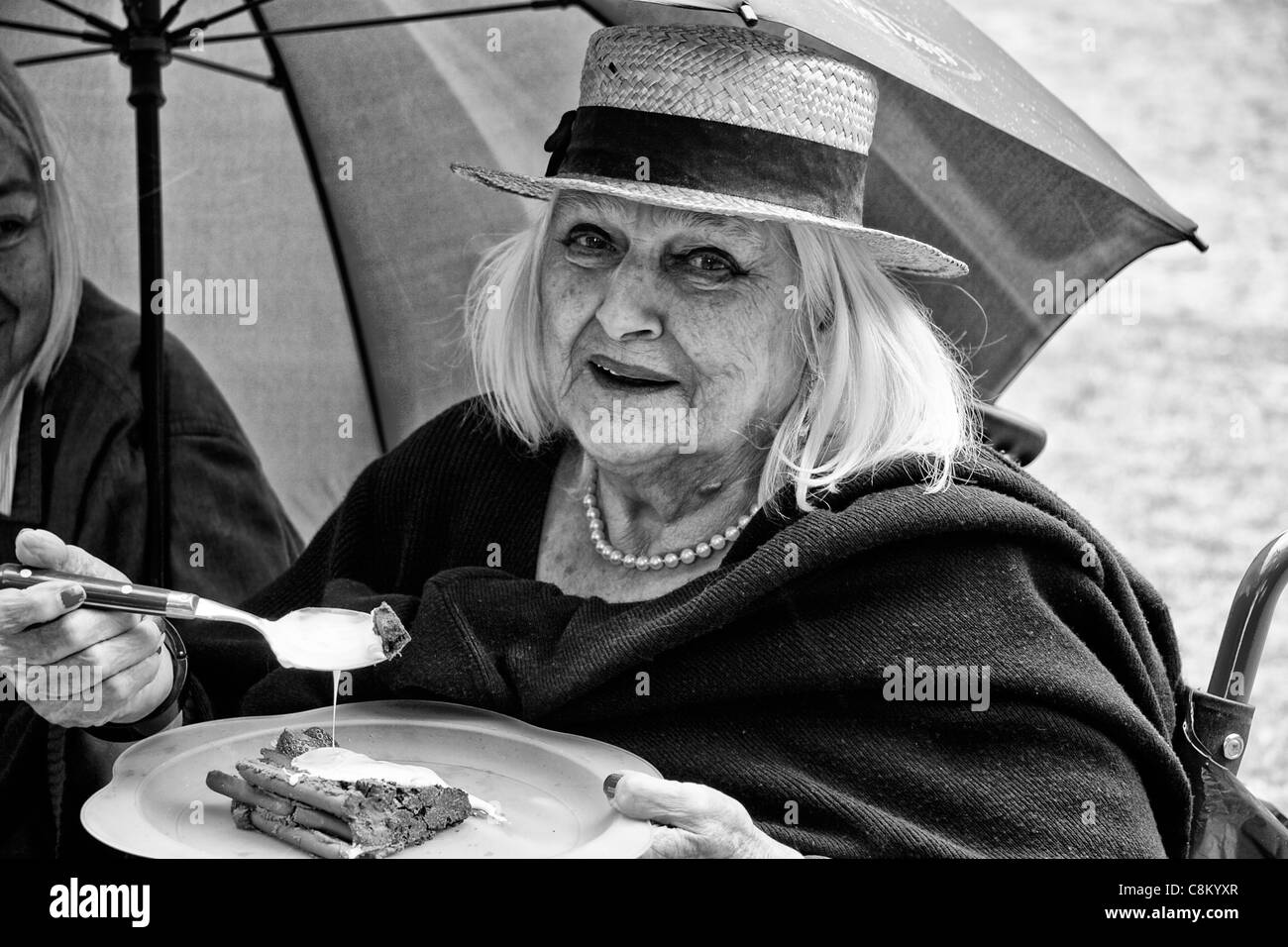 Elderly woman wearing a straw boater eating chocolate cake - Stock Image