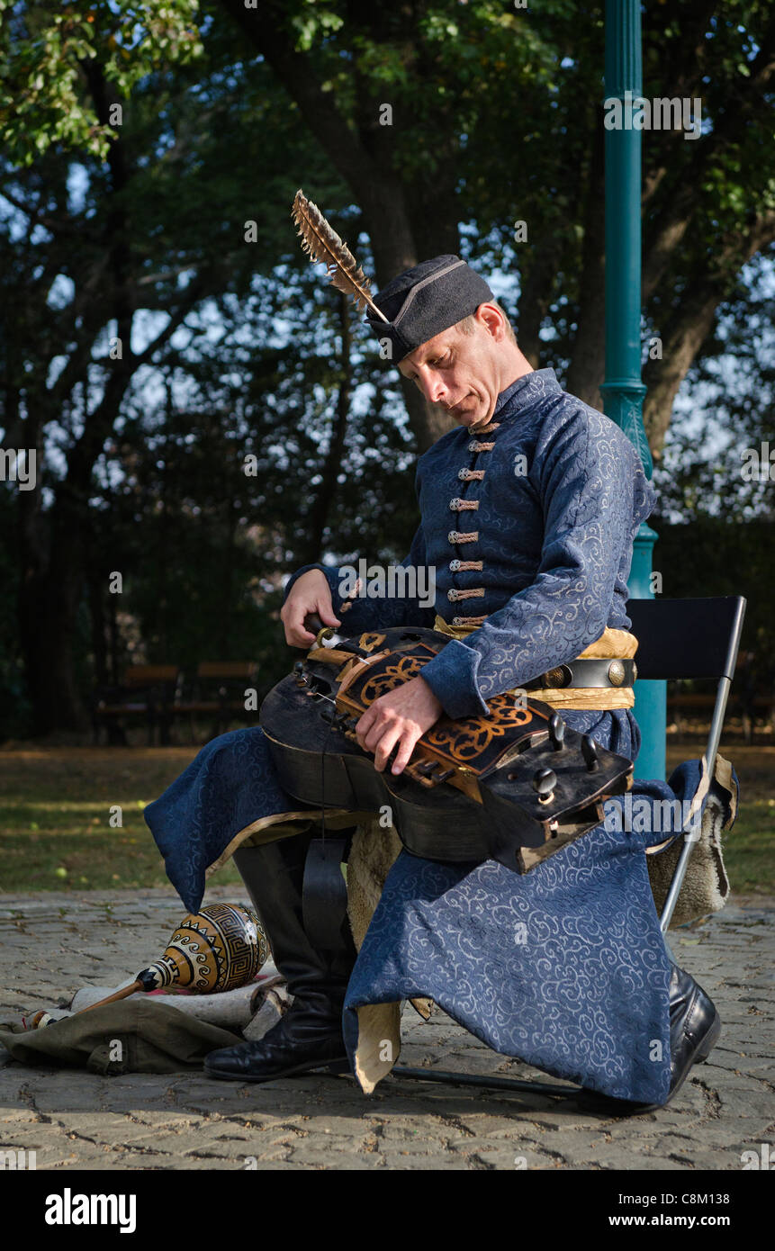 Street musician in traditional costume playing a Hurdy Gurdy in a park in Budapest - Stock Image