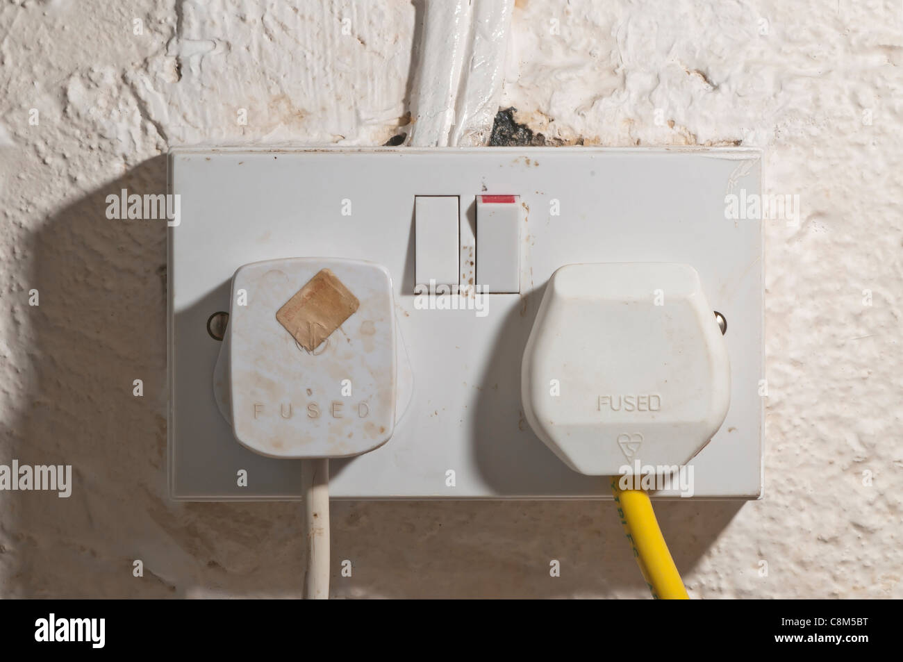 British twin electric socket and fused plugs, old wiring. - Stock Image
